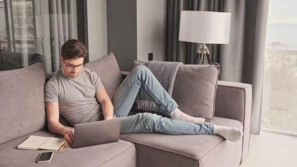 Junger konzentrierter Mann zu Hause mit Laptop
