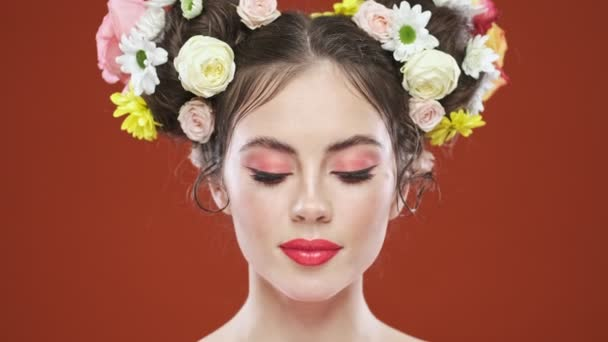 A charming young brunette woman with an amazing floral hairstyle is opening her eyes and looking to the camera isolated over red background in studio