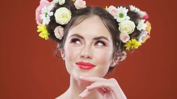 A dreaming young brunette woman with an amazing floral hairstyle is posing to the camera isolated over red background in studio