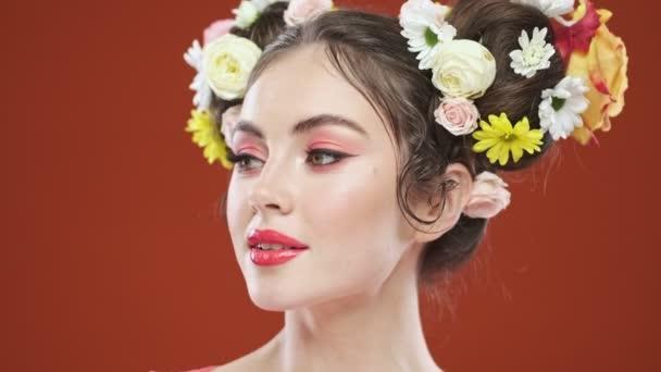 Atraktivní mladá brunetka žena s úžasným květinovým účesem se dívá stranou izolované přes červené pozadí ve studiu