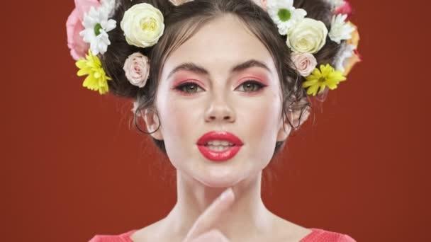 Dokonalá mladá brunetka žena s úžasným květinovým účesem dělá gesto mlčení izolované nad červeným pozadím ve studiu