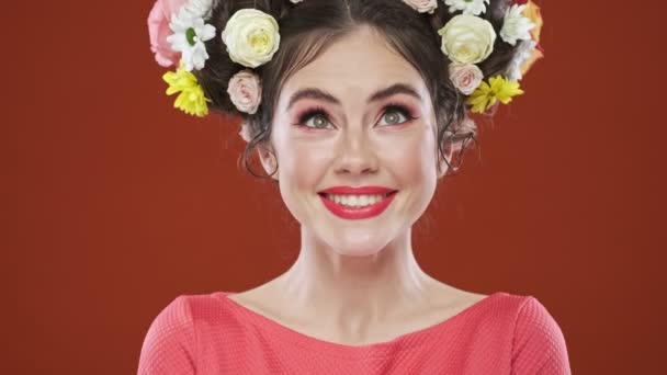 A cheerful brunette woman with an amazing floral hairstyle is posing to the camera with different facial emotions isolated over a red background in studio