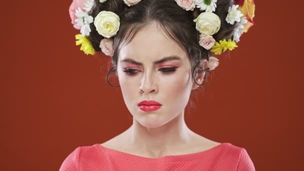 An angry mad brunette woman with an amazing floral hairstyle is looking to the camera isolated over a red background in studio