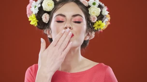 A gorgeous smiling brunette woman with an amazing floral hairstyle is sending an air kiss to the camera isolated over a red background in studio