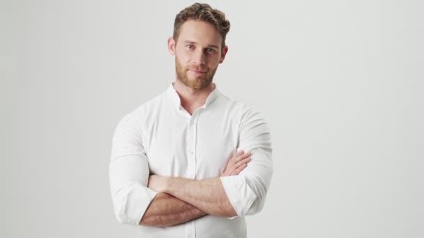 Jóképű fiatal pozitív boldog férfi fehér ing elszigetelt felett fehér fal háttér