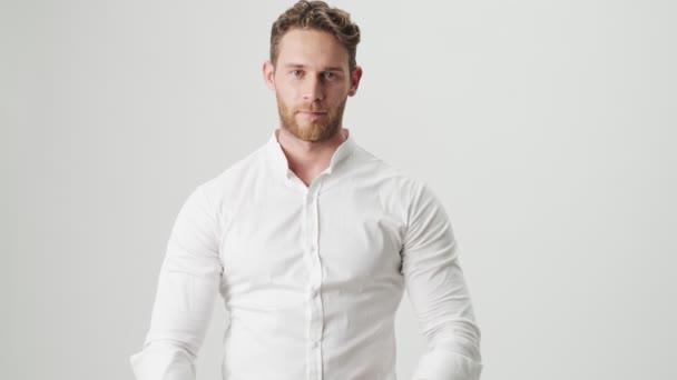 Schöner junger, glücklich lächelnder Mann in weißem Hemd isoliert über weißem Wandhintergrund