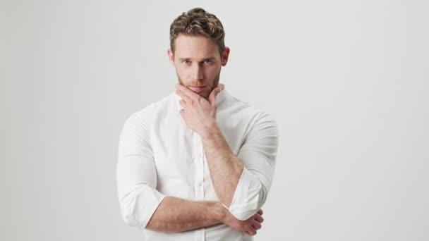 Schöner junger fröhlicher Mann in weißem Hemd isoliert über weißem Wandhintergrund