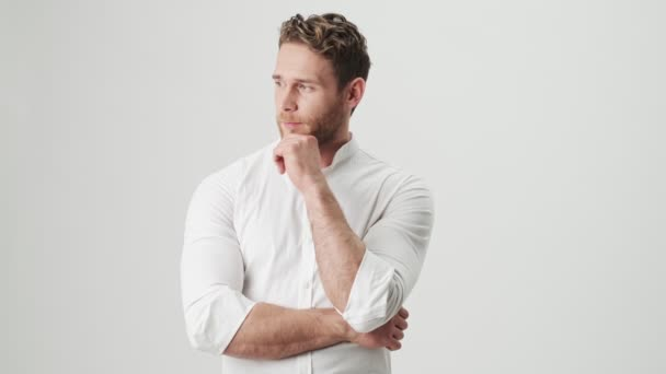 Handsome young optimistic man in white shirt isolated over white wall background