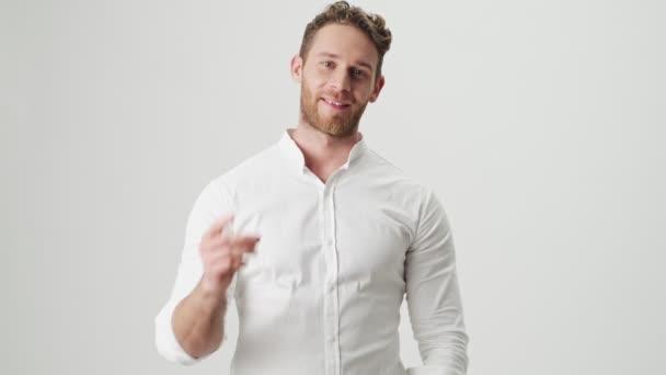 Fešák mladý veselý muž v bílé košili izolované přes bílou zeď pozadí