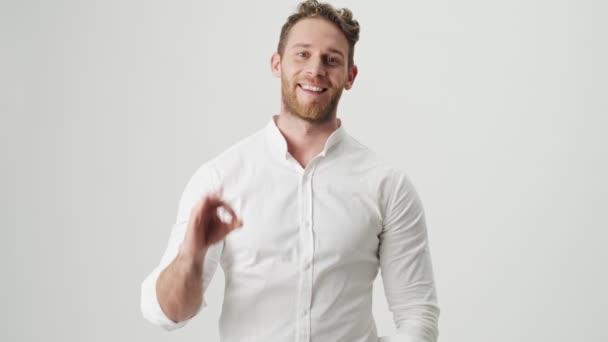 Jóképű fiatal elégedett boldog férfi fehér ingben elszigetelt felett fehér fal háttér