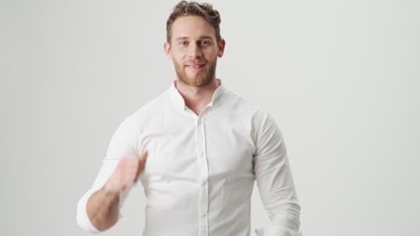 Hezký mladý usmívající se muž v bílé košili izolované přes bílou zeď pozadí