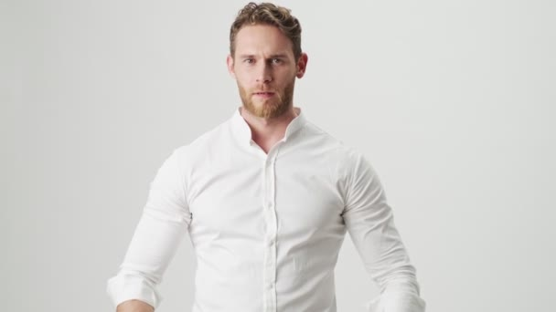 Handsome young displeased man in white shirt isolated over white wall background showing thumbs down