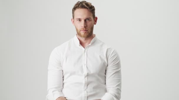 Hezký mladý zmatený muž v bílé košili izolované přes bílou zeď pozadí