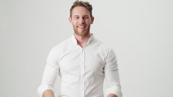 Schöner junger optimistischer Mann in weißem Hemd isoliert über weißem Wandhintergrund