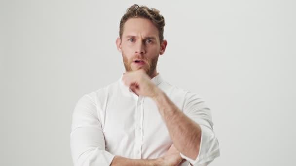 Fešák mladý seriózní muž v bílé košili izolované přes bílou zeď pozadí ukazující stop gesto