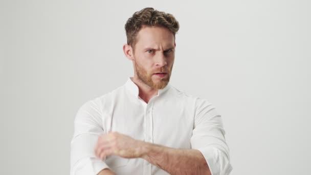 Hezký mladý seriózní muž v bílé košili izolované přes bílou zeď pozadí říká ne