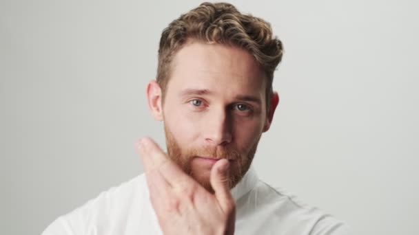 Jóképű fiatal vidám pozitív férfi fehér ing elszigetelt felett fehér fal háttér