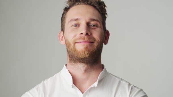 Fešák mladý pozitivní úsměv muž v bílé košili izolované přes bílou zeď pozadí