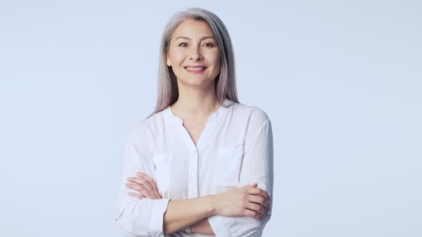 A successful old mature woman with long gray hair wearing formal business clothes is doing an OK gesture standing isolated over white background in studio