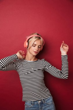 Image of nice happy woman with headphones listening music and dancing isolated over red background