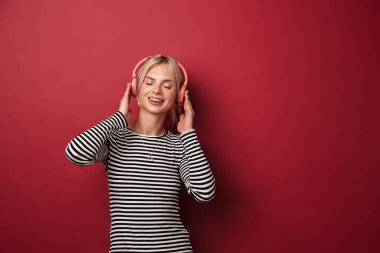 Image of nice smiling woman with headphones listening music and dancing isolated over red background