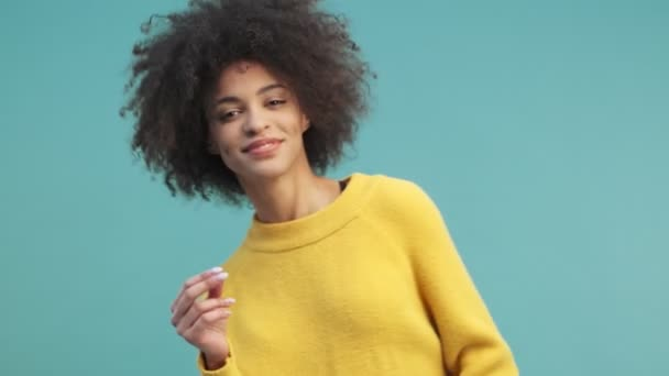 A cheerful young african american woman with curly hair is dancing isolated over blue wall background in studio