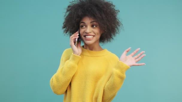 Eine lächelnde positive junge afrikanisch-amerikanische Frau mit lockigem Haar telefoniert isoliert über blauem Wandhintergrund im Studio