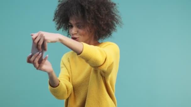 Eine hübsche junge afrikanisch-amerikanische Frau mit lockigem Haar spielt auf ihrem Smartphone isoliert über blauem Wandhintergrund im Studio
