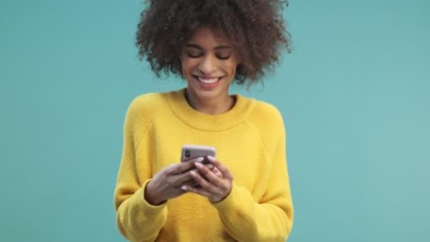 Eine attraktive junge afrikanisch-amerikanische Frau mit lockigem Haar beobachtet etwas Lustiges auf ihrem Smartphone und lacht isoliert vor blauem Wandhintergrund im Studio