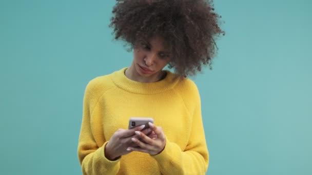 Eine wütende junge Afroamerikanerin mit lockigem Haar tippt auf ihrem Smartphone, das isoliert vor blauem Wandhintergrund im Studio steht