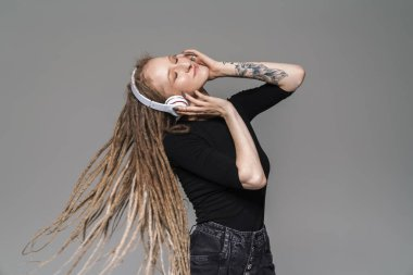 Portrait of an attractive smiling young woman with dreadlocks standing isolated over gray background, listening to music with wireless headphones