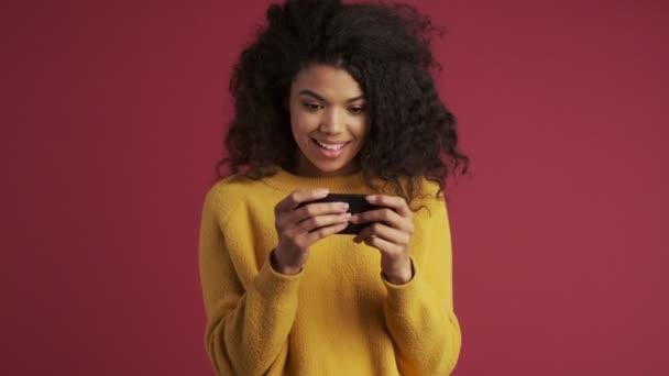 Junge afrikanische lachende zufriedene Frau isoliert über dunkelrotem weinrotem Hintergrund Videos per Handy ansehen