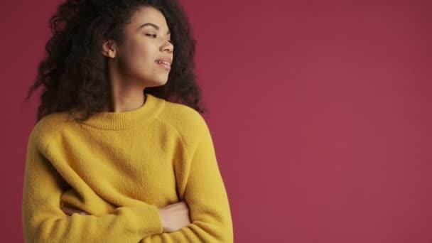 Fiatal afrikai vidám pozitív nő elszigetelt sötét vörös burgundi háttér néz félre
