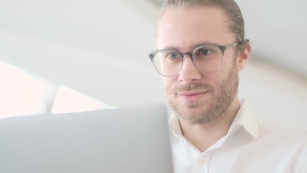 Detailní pohled na atraktivního mladého podnikatele, který nosí brýle, používá svůj notebook v kavárně ve městě