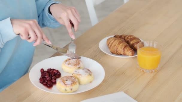 Oříznutý pohled na mladou ženu je jíst sýrové palačinky sedí v bílé kuchyni doma
