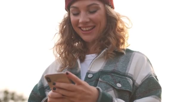 Lächelnde blonde Frau mit Hut und kariertem Hemd mit Smartphone und Blick nach draußen