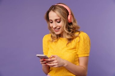 Image of cheerful woman smiling while using headphones and cellphone isolated over purple background