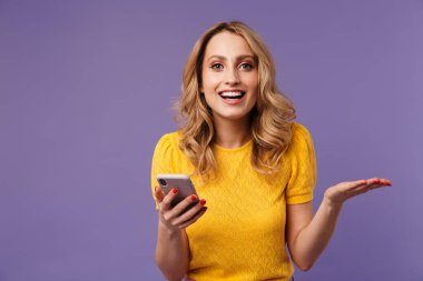 Image of excited pretty woman smiling while holding copyspace and cellphone isolated over purple background