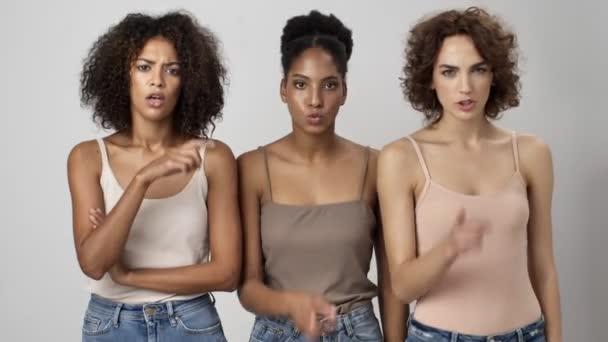 Tři vážné multietnické ženy ukazují gesto mlčení stojící izolovaně nad bílým pozadím