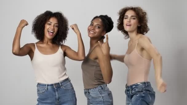 Tři atraktivní multietnické ženy ukazují své svaly pózující na kameru stojící izolovaně nad bílým pozadím