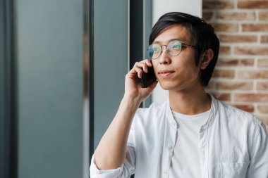 Image of handsome young asian man wearing eyeglasses talking on cellphone while standing by window in office
