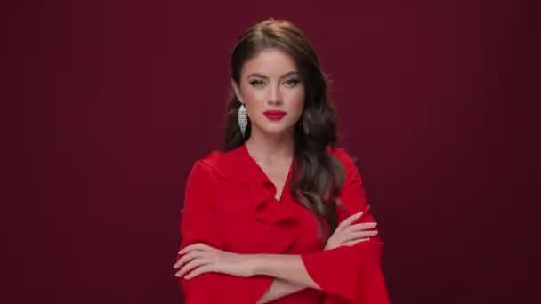 Eine hinreißende Frau in rotem Kleid lächelt und blickt vereinzelt in die Kamera vor weinrotem Hintergrund