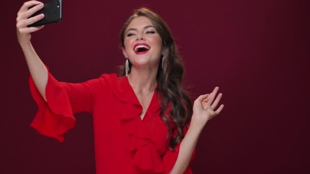 Eine modische attraktive junge Frau in einem roten Kleid macht Selfie-Fotos mit ihrem Smartphone vor weinrotem Hintergrund