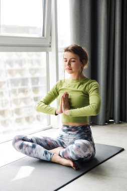 Photo of focused young woman meditating while doing yoga exercises on mat in cozy room