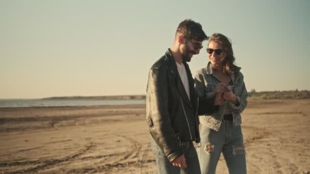 Šťastný mladý pár muž a žena v lásce jsou chůze na pláži během jízdy na motorce