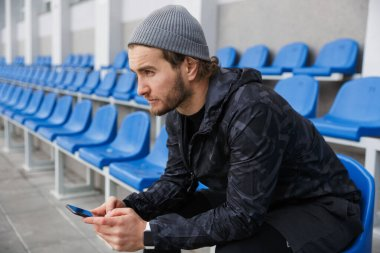Confident young sportsman sitting on tribune seats at the stadium, using mobile phone