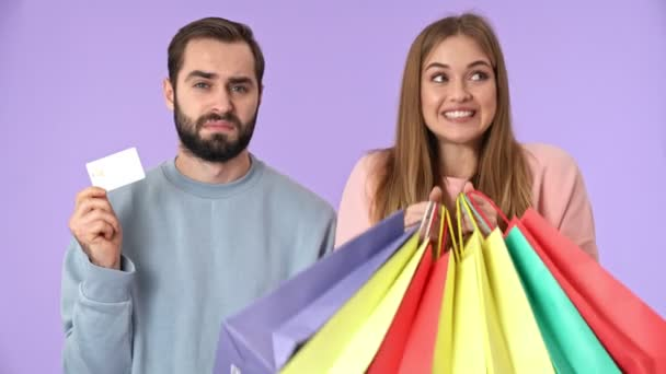 Happy blonde woman posing and enjoying the moment with purchases while standing near the displeased bearded man which holding credit card over purple background
