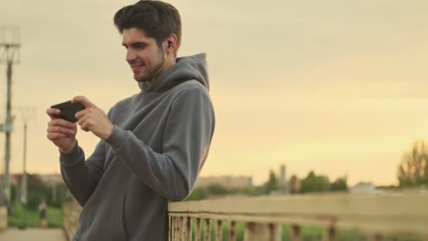 Usmívající se mladý sportovec se dívá na video na svém smartphonu při chůzi po mostě
