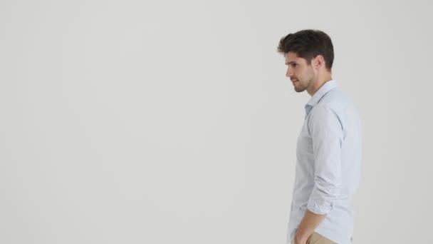 Vážný mladý muž kráčí z jedné strany na druhou, pak se dívá do kamery a zastaví se izolovaný přes bílé pozadí