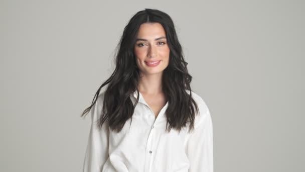 Krásná mladá žena se usmívá stojí izolovaně přes šedé pozadí